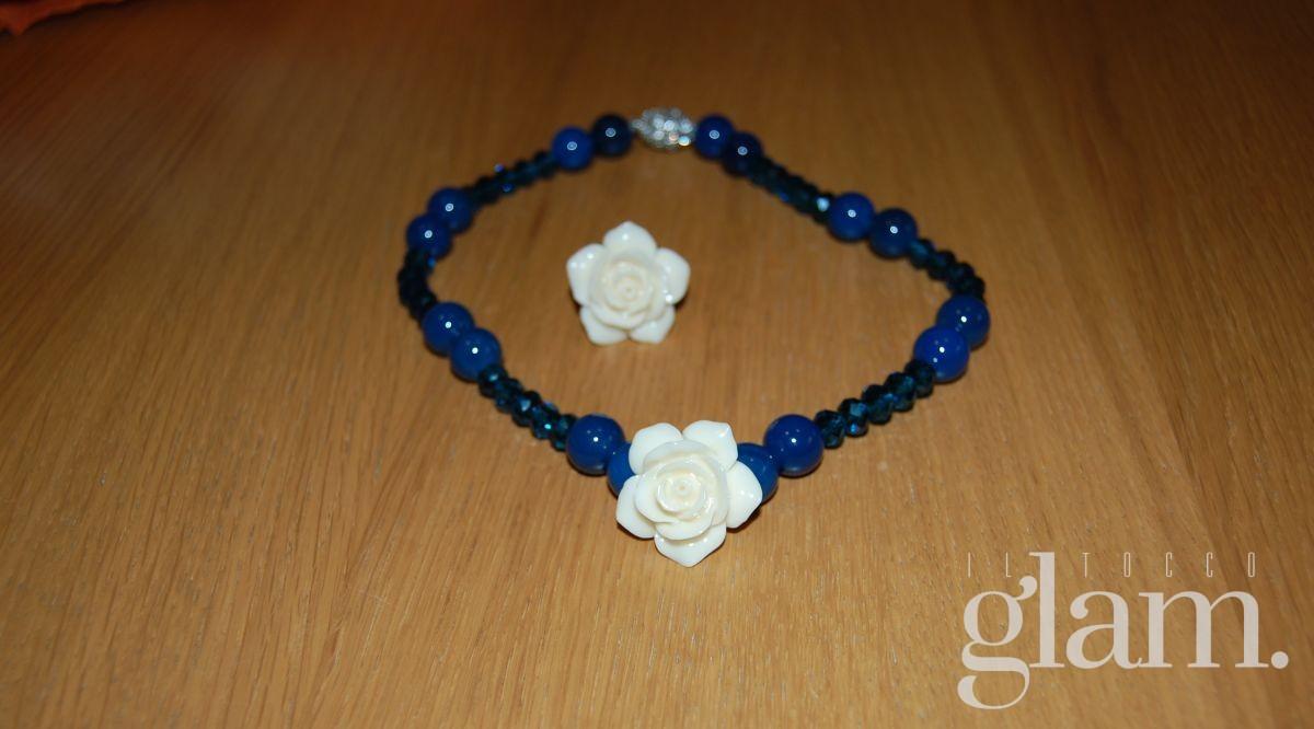 Collana con pietre blu e rosa bianca, chiusura a calamita. Anello con cerchietto regolabile.